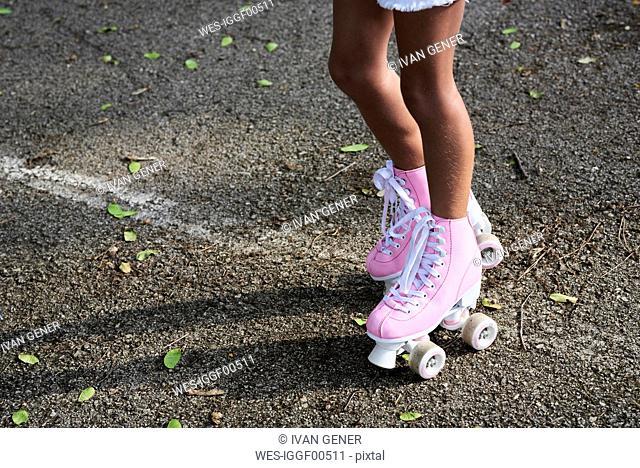 Little girl wearing pink roller blades, rollerskating