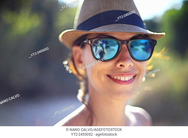 Attractive young woman wearing a straw hat and sunglasses on the beach, Ibiza, Balearic Islands, Spain