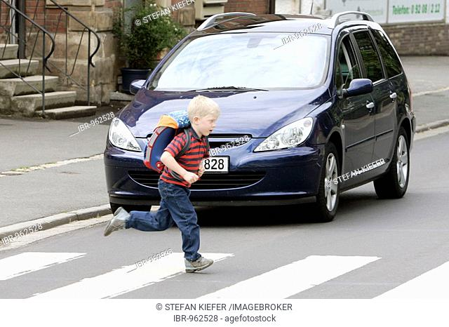 Schoolchild running over a pedestrian crossing while a car is waiting, Bayreuth, Bavaria, Germany, Europe