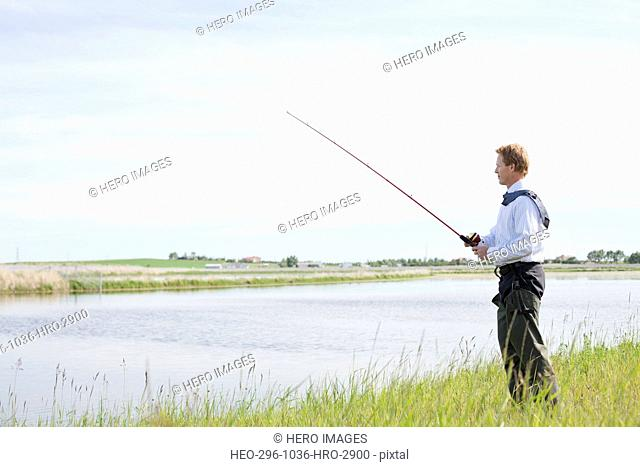 Businessman fishing by river