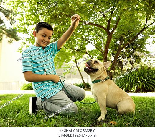 Mixed race boy playing with dog