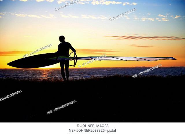 Silhouette of windsurfer standing on beach