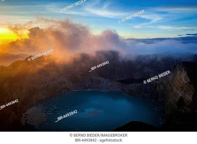 Sunrise at Kelimutu volcano, mist over crater with crater lake, Kelimutu National Park, Flores, East Nusa Tenggara, Indonesia