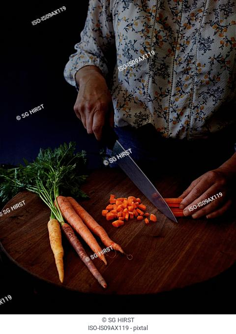 Cropped view of woman slicing carrots with kitchen knife