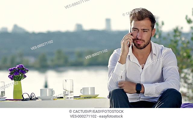 Handsome man talking on the phone outdoors