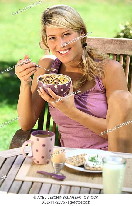 portrait of woman having breakfast in garden eating muesli