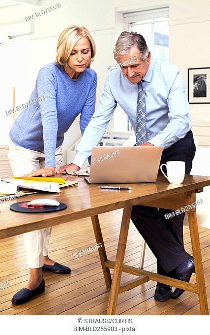 Caucasian business people leaning on table using laptop