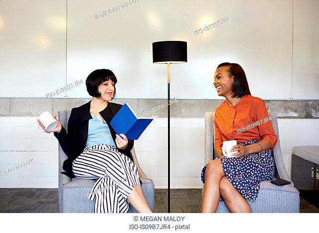 Two businesswomen sitting in comfortable chairs in office, having coffee break