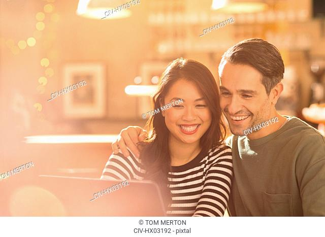Smiling couple video chatting at laptop in cafe