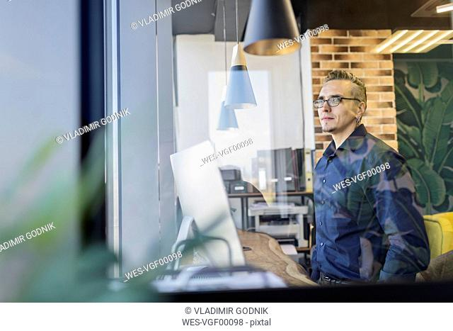 Man standing in office looking out of window