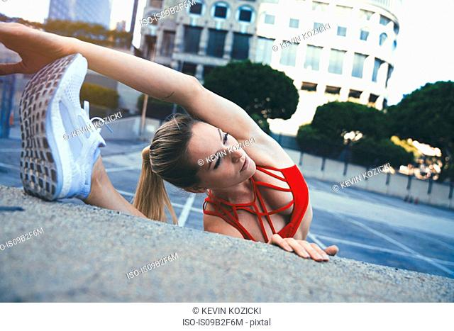 Young woman stretching against wall outdoors