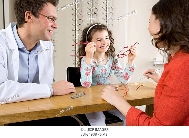 Optometrist and mother watching girl try on eyeglasses