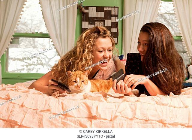 Teenage girls lying on bed with smartphone