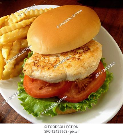 Grilled chicken sandwich with tomato and lettuce with French fried potatoes