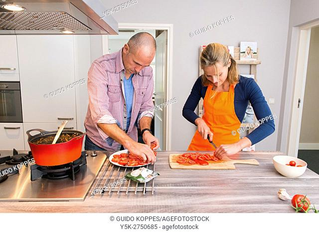 Kaatsheuvel, Netherlands. Mid adult man and woman preparing tomatoes for a sidedish with Lasagna dis dinner