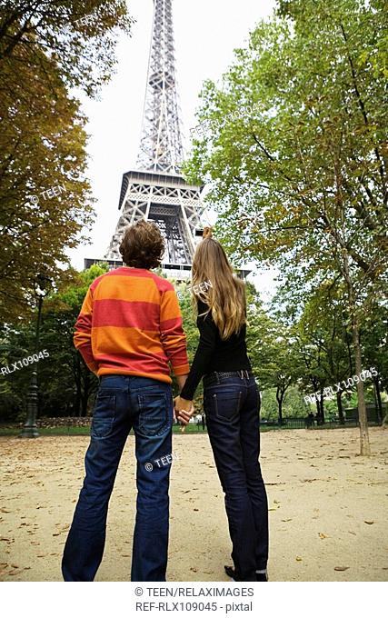 Rear view of young couple standing under Eiffel tower, Paris, France