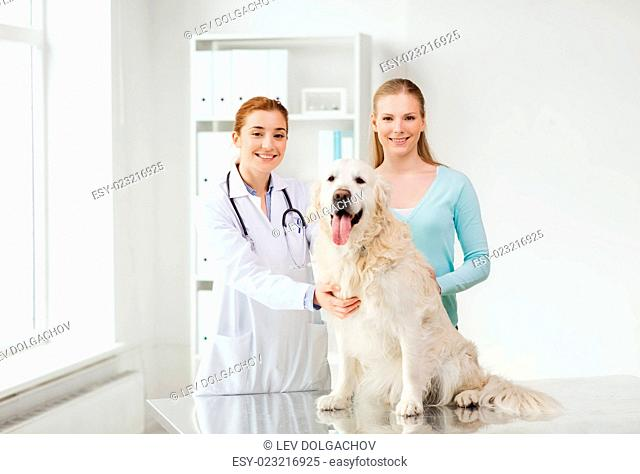 medicine, pet, animals, health care and people concept - happy woman with golden retriever dog and veterinarian doctor at vet clinic