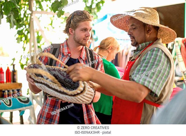 Market trader selling bag to tourist