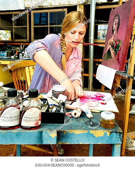 Blonde Woman Mixing Paints in a Painter's Studio with Paint Brush in Her Mouth