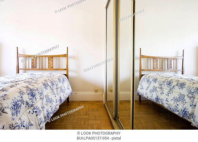 Small twin bed next to mirrored closet doors