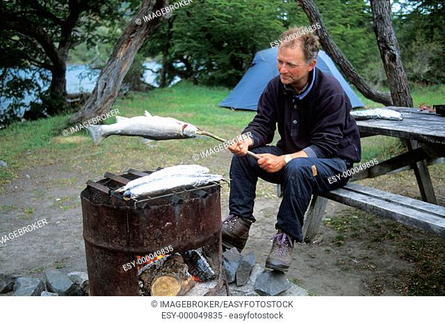 Man barbecueing a salmon trout, Torres del Paine National Park, Patagonia, Chile