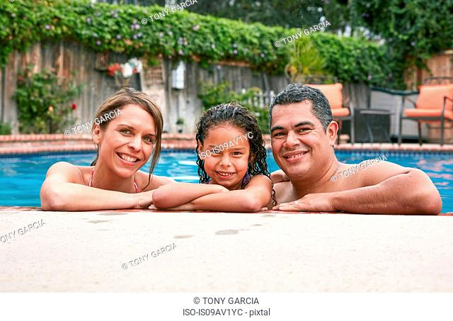 Head and shoulders of girl in swimming pool with parents looking at camera smiling