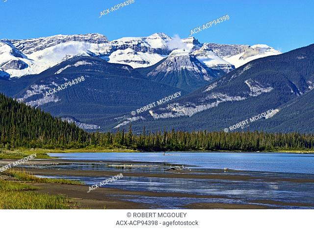 A late summer landscape image looking to the west end of Jasper Lake with snow-capped rocky mountains of Jasper National Park in the background