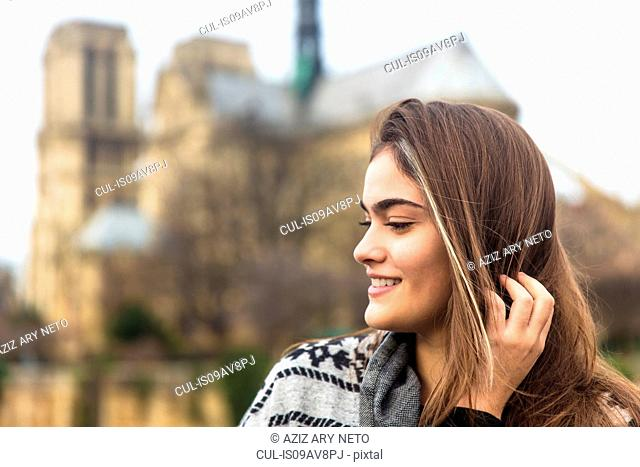 Side view of young woman, Notre Dame Cathedral in background, Paris, France