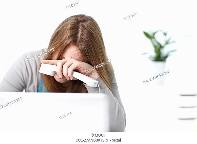 Depressed girl sitting behind laptop