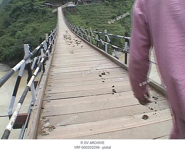 Men with horses cross a high suspension bridge in the Himalayas