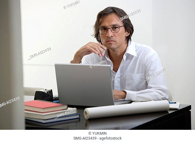 Businessman using laptop at the desk, looking at camera