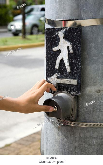 Man pressing button of pedestrian crossing sign