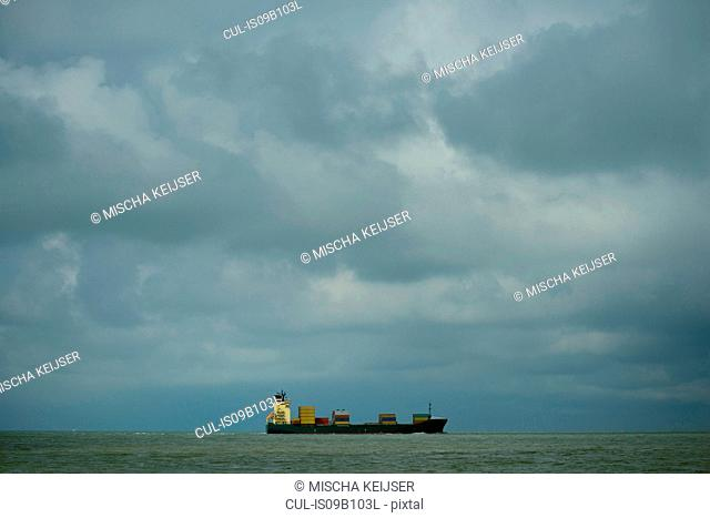 Container ship sailing toward bad weather, Domburg, Zeeland, Netherlands
