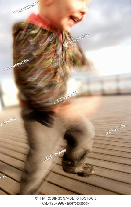4 year boy jumping for joy on pier