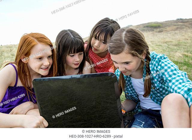 Schoolgirls using laptop together during field trip
