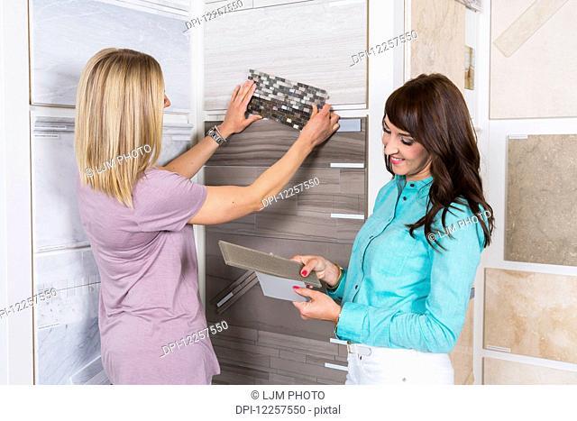 Design consultant and interior designer selecting tiles in showroom of tile store; Edmonton, Alberta, Canada