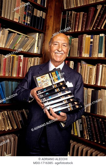 Valentino Bompiani in his home studio with some books in hand. Italian publisher and playwright Valentino Bompiani, executive of the review Sipario