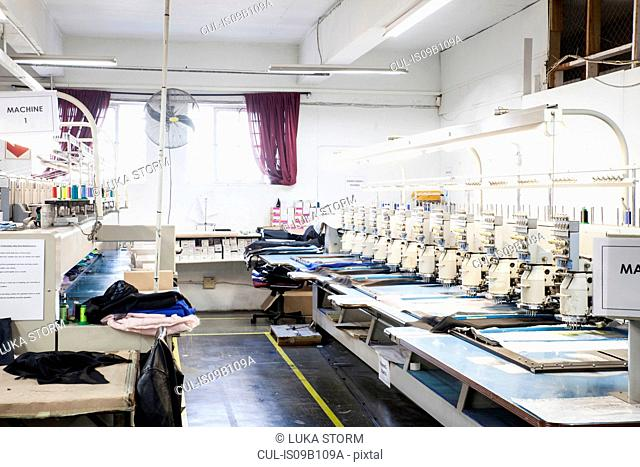 Rows of programmed embroidery machines speed stitching cloth in clothing factory