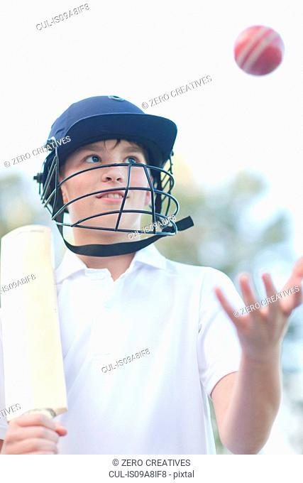 Boy wearing helmet catching cricket ball