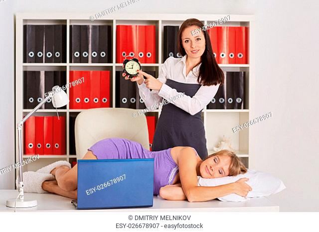 Young business woman tries to wake the sleeping coworker on a workplace in the office. Overworked