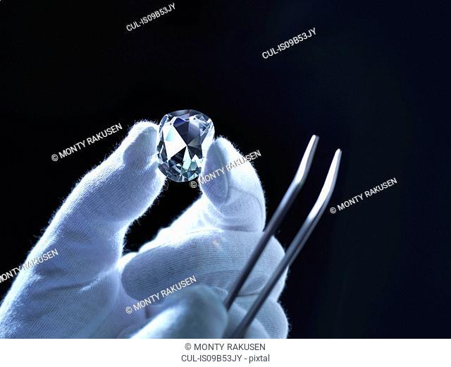 Jeweller inspecting replica diamonds with gloved hand