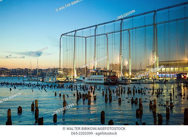 USA, New York, New York City, Lower Manhattan, golf driving range on the Hudson River, dusk