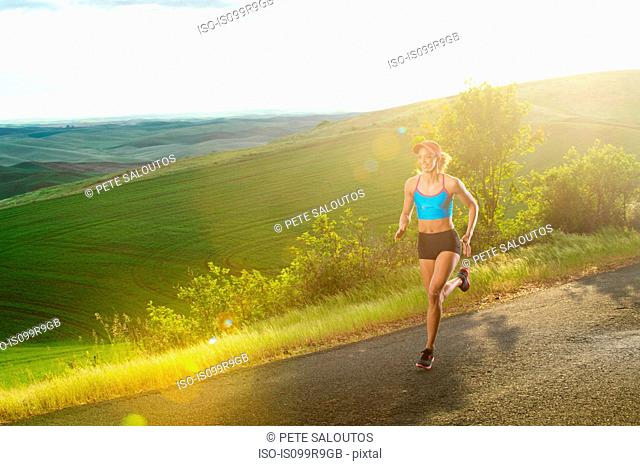 Young woman running in landscape of Palouse Hills, Washington, USA