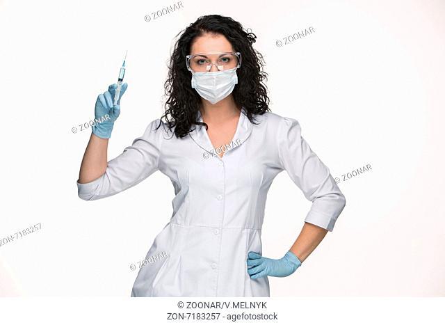 Portrait of lady surgeon showing syringe over white background