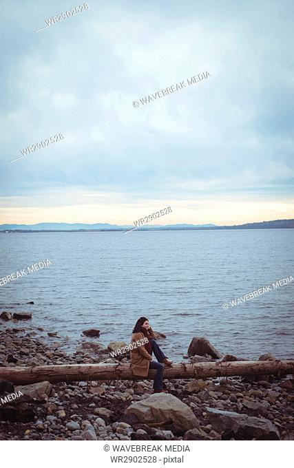 Woman relaxing on driftwood against cloudy sky