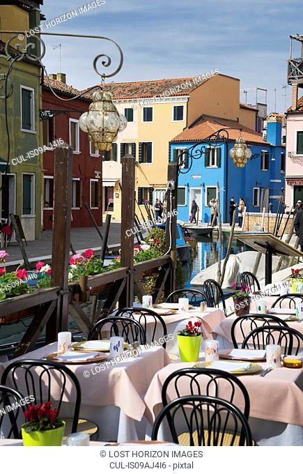 Multi colored houses and sidewalk restaurant, Burano, Venice, Veneto, Italy