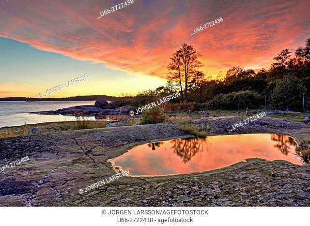 Sweden, Smaland, Navelso, Puddle reflecting sunset