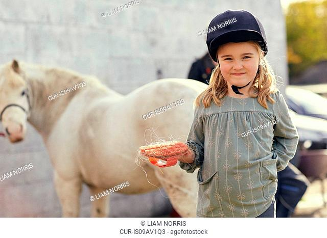 Portrait of girl and pony at stable
