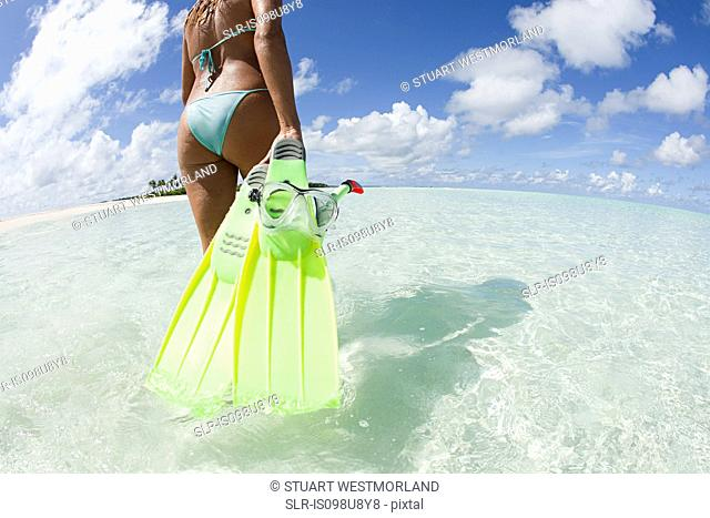 Woman with swimming flippers on Kadhdhoo Island, Laamu Atoll, Maldives
