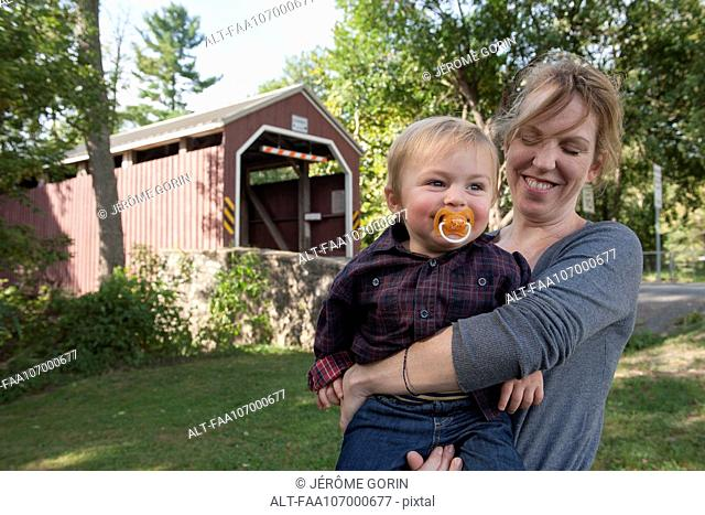 Mother holding toddler son in front of covered bridge, portrait